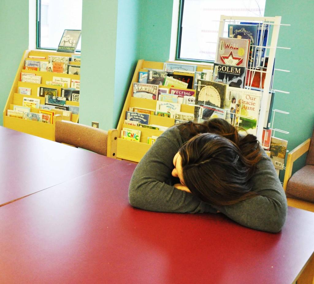 A student napping in the library due to the lack of sleep.