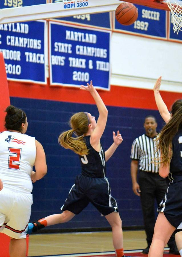 Lohr, number 3, and Kendall Bresee, number 33, watch Lohr as she makes her 1000th career point at Urbana.