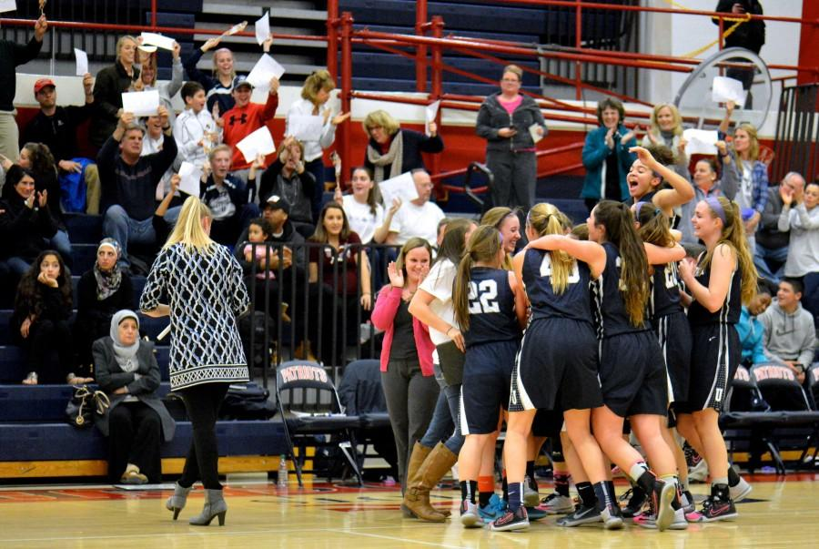 Players and coaches celebrate after Lohr scores her 1000th career point, in a game against Governor Thomas Johnson High School.