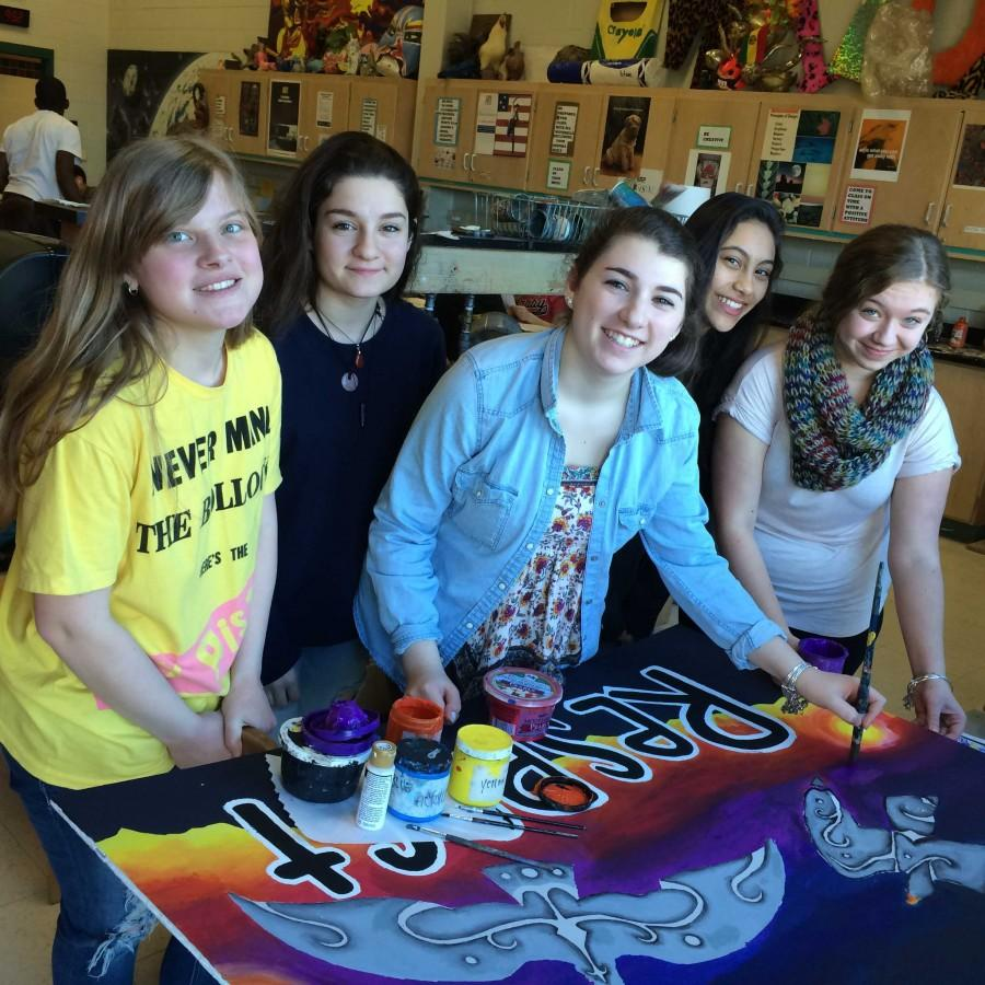 National Art Honor Society posed with one of  their murals.