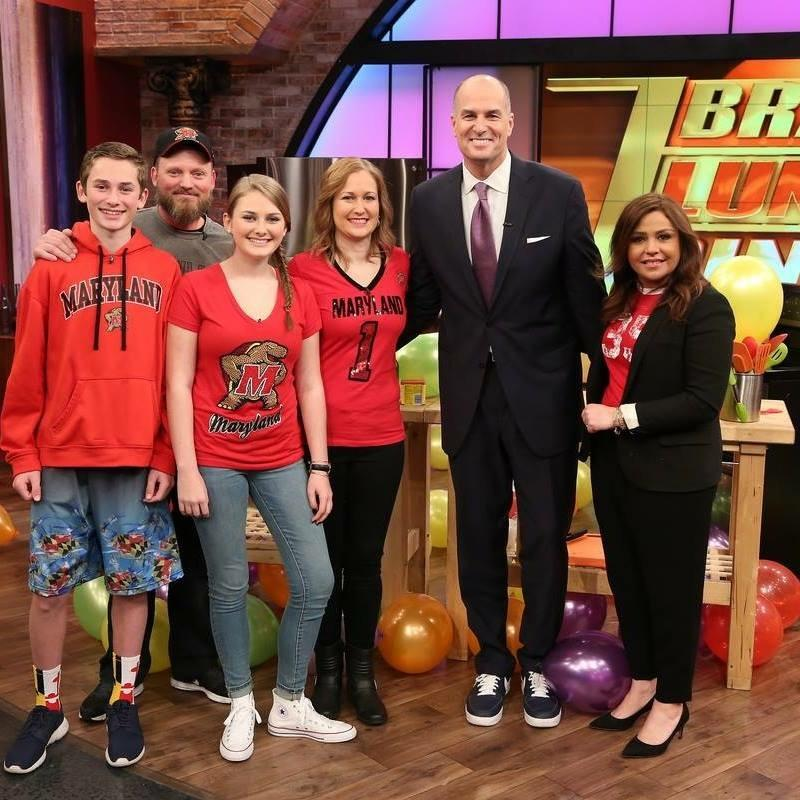 The Harper family poses with Rachael Ray and Jay Bilas after finishing the March Madness cook-off