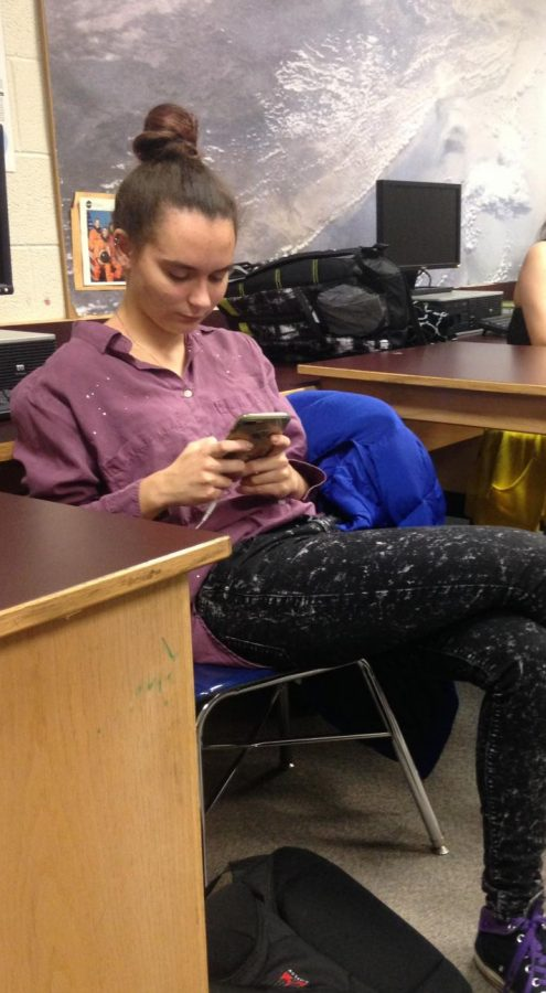 Daryna, a sophomore at UHS, using her phone before class.