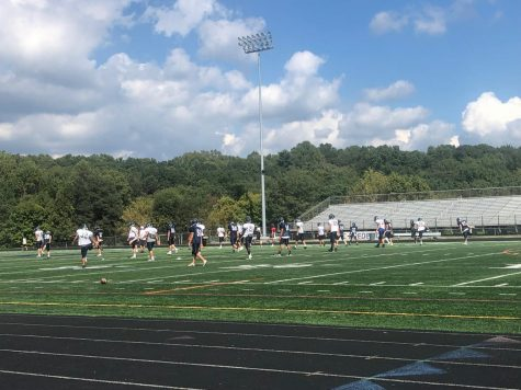 Varsity football players stretch before starting practice.