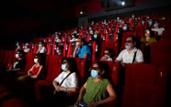 People social distancing with masks while watching a movie.