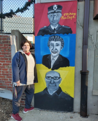 Tobias Weichbrod (11) stands beside his completed mural at Mt. Airy